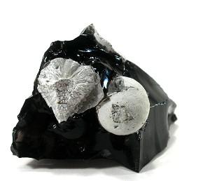 Ein Obsidian mit Cristobalit als offene und geschlossene Kugel.